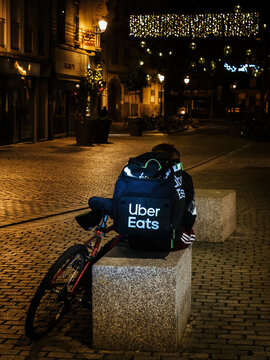 Strasbourg, France - Nov 29, 2019: Lonely uber eats app driver delivery young man sitting on the stone urban furniture eating at night - city background