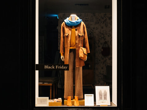 Strasbourg, France - Nov 29, 2019: Fashion store shwocase with female clothes and discrete text Black Friday