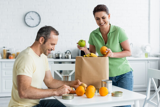 Man holding food near cheerful wife and paper bag in kitchen