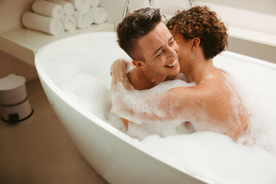 Smiling young queer couple enjoying a bubble bath together