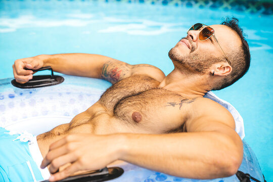 A Young mexican and sexy muscular man posing in the swimming pool
