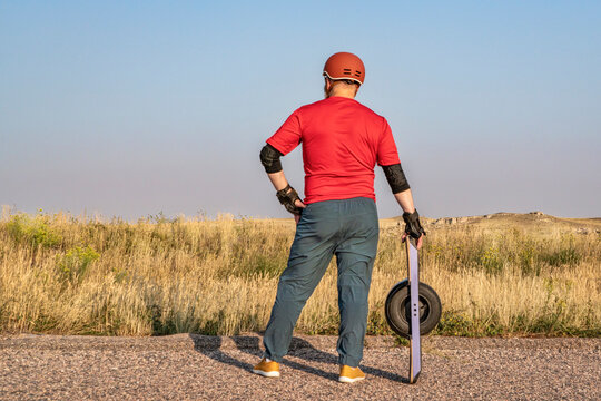 mature senior male with one-wheeled electric skateboard on a prairie road, late summer scenery with haze and smoke from distant wildfires