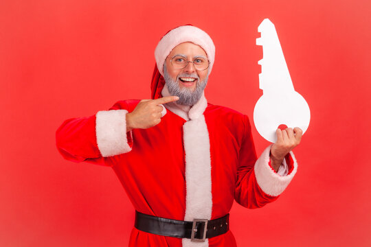 Portrait of smiling elderly man with gray beard wearing santa claus costume standing pointing to paper key, recommend agency for buying apartment. Indoor studio shot isolated on red background.