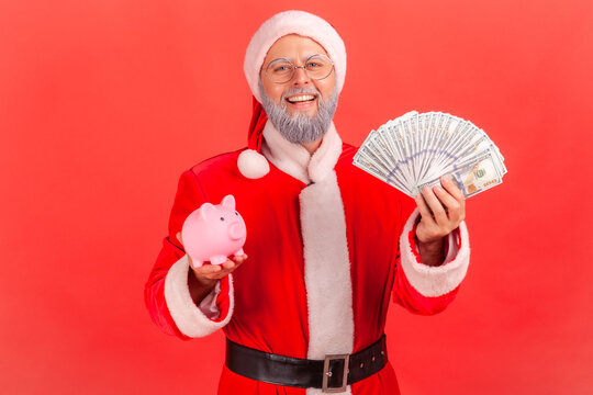Positive smiling elderly man with gray beard wearing santa claus costume holding dollars banknotes and piggy bank, being happy of savings. Indoor studio shot isolated on red background.