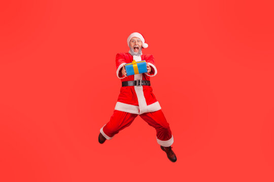 Positive elderly man with gray beard wearing santa claus costume jumping high with wrapped present box, giving gift for Christmas, looking at camera. Indoor studio shot isolated on red background.
