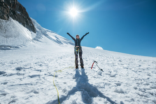 The woman raised her arms and cheerfully smiling while ascending Mont Blanc (Monte Bianco) summit dressed in mountaineering clothes with a climbing harness on the snowy Mont Blanc du Tacul slopes.