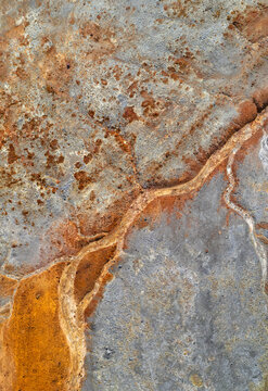 Dry rusty river bed over grey mine tailings, acid mine drainage vertical texture