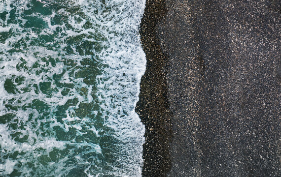 Sea waves breaking on wild beach with black sand and pebbles, aerial natural background
