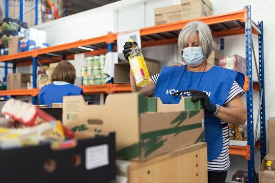 Volunteer woman preparing food packages