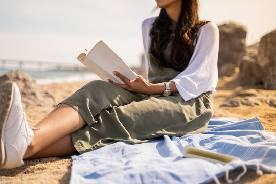 Beautiful young woman relaxing reading book at beach