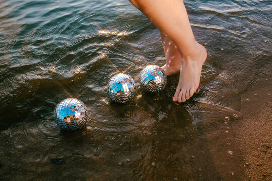 feet in the sea with mirror balls