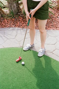 Woman Plays Miniature Golf