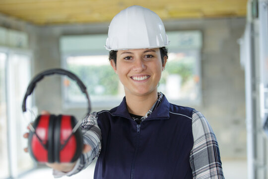 female construction worker showing protective headphones