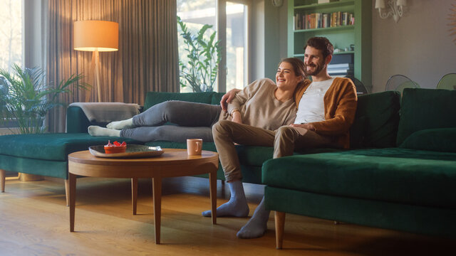 Couple Watches TV together while Sitting on a Couch in the Living Room. Girlfriend and Boyfriend embrace, cuddle, talk, smile and watch Television Streaming Services. Home with Cozy Stylish Interior.