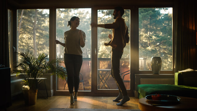 Happy Young Couple Dances in the Living Room. Cheerful Girlfriend and Boyfriend Enjoy True Love, Good Mood and Energetic Music Have Fun at Home. Stylish Interior and Sunny Day