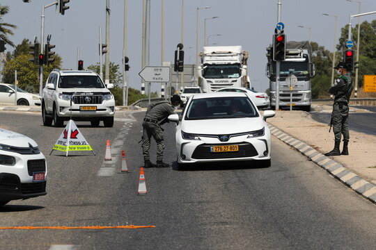 Israeli security force members stop a car at a roadblock as part of search efforts to capture six Palestinian men who had escaped from Gilboa prison earlier this week, in northern Israel