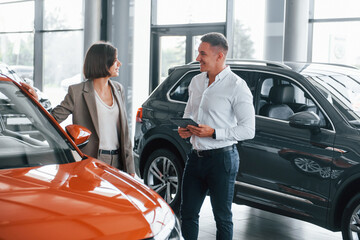 Orange colored car. Man in formal wear helping customer with choice of the automobile