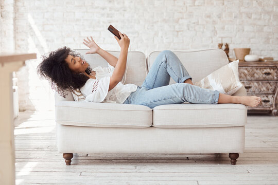 Happy black woman in headphones looking at smartphone, enjoying video meeting with friends and colleagues, online virtual conversation concept. Female student lying on sofa and making video call.