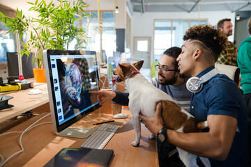 Fototapeta Man holding dog, sitting at computer with colleague obraz