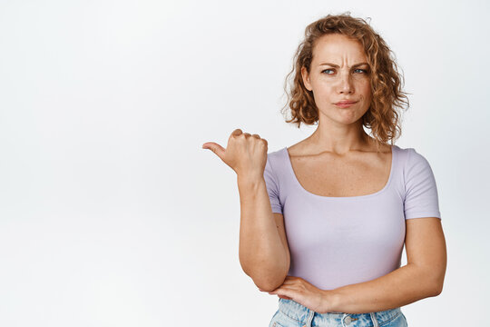 Relucrant blond girl frowning, pointing and looking left with disappointed face expression, standing in t-shirt over white background