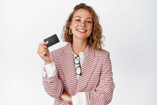 Happy female manager shows credit card and smiles pleased, stands in suit against white background