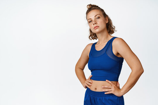 Portrait of sportswoman workout, standing confident in sportsbra with hands on waist, looking determined at camera, white background