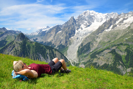 Tourist lying on a meadow in sunny day, at the background Mont Blanc ( Monte Bianco ) mountain range. Aosta valley, Italy.