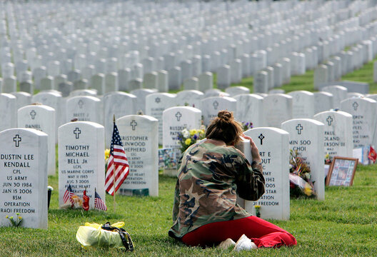 Woman cries at grave of soldier killed in Iraq at Arlington National Cemetery