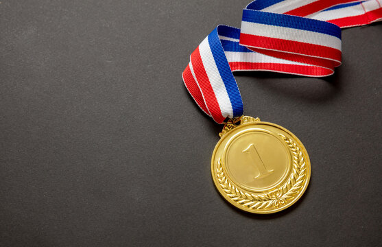 Gold medal. Champion trophy award and ribbon. Prize in sport for winner isolated on black background