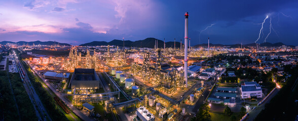 twilight cityscape panorama Oil and GAS refinery industry factory zone and storage tank with container train railroad tracks at night scene blue sky and cloud storm background