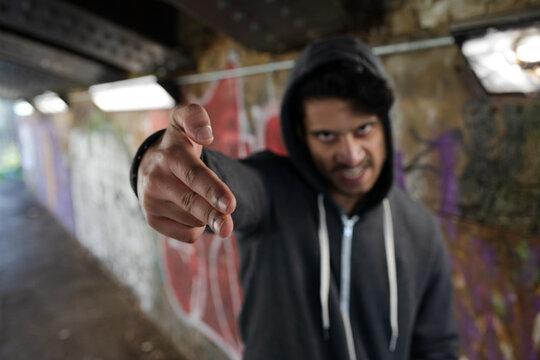 Portrait menacing young man gesturing finger gun in urban tunnel