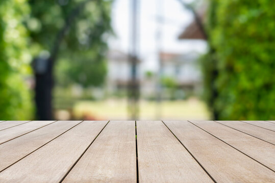 Empty old wooden table in front of blurred tree, bokeh background in the garden. Can be used for display or montage for show your products.