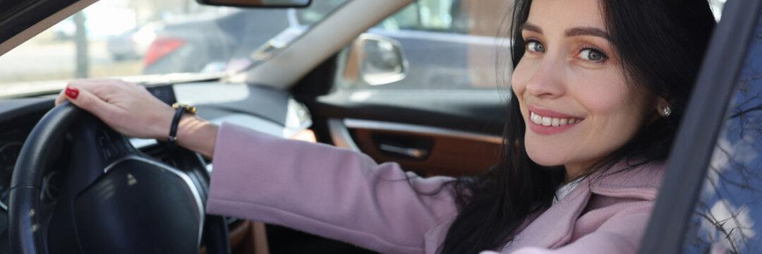 Portrait of smiling woman driving car closeup