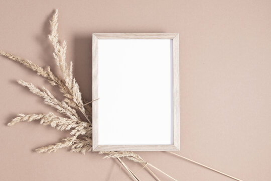 Wooden photo frame mockup with dry plant on beige background. Autumn composition. Flat lay, top view, copy space