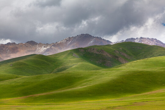 landscape with grasslands, rolling hills and mountains, on the high altitude plateau of Qinghai, China