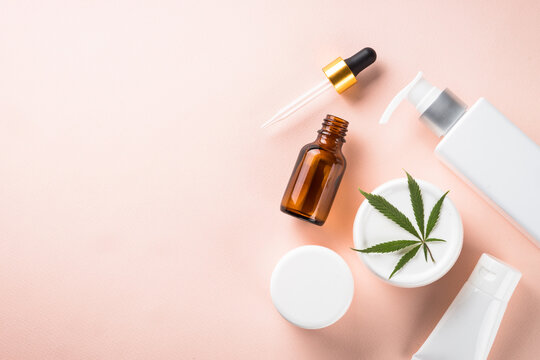 Cannabis cosmetic products. Natural cosmetic. Cream, soap, serum and others. Flat lay image on pink background.