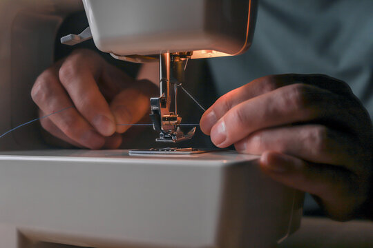 Male hands inserting thread through needle hole in sewing machine, starting his work.