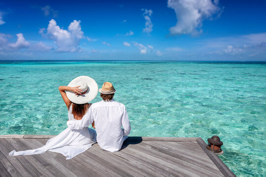 A couple on holiday time sits on a pier and enjoys the view to the turquoise ocean of the tropical Maldives islands