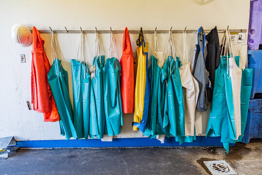 Colorful waterproof aprons hanging on hooks.