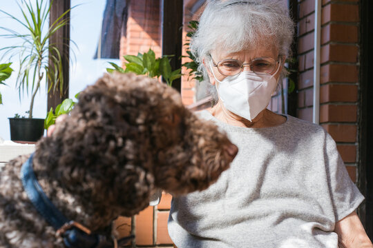 old woman wearing face mask holding her dog