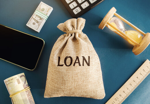 Money bag with the word Loan. The concept of accumulation of money for the payment of credit debt. Mortgage lending. Savings. Family budget. Real Estate Concept