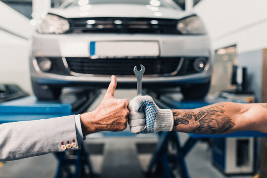 Close up shot of car mechanic worker's and business man costumer's hands showing thumb up sign during periodic car condition check.