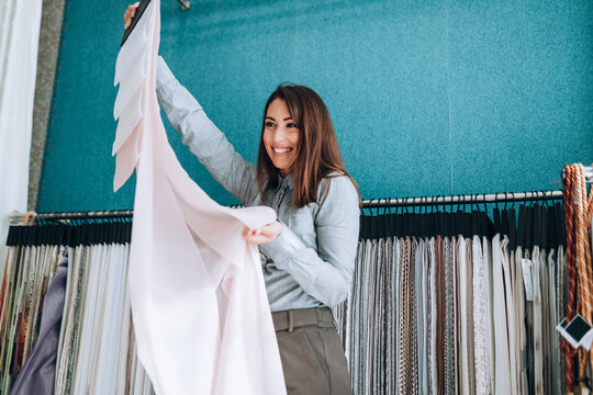 Young woman designer chooses fabrics for curtains in textile show room.