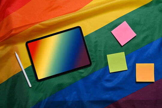 Digital tablet with blurred gradient mesh screen on rainbow flag.