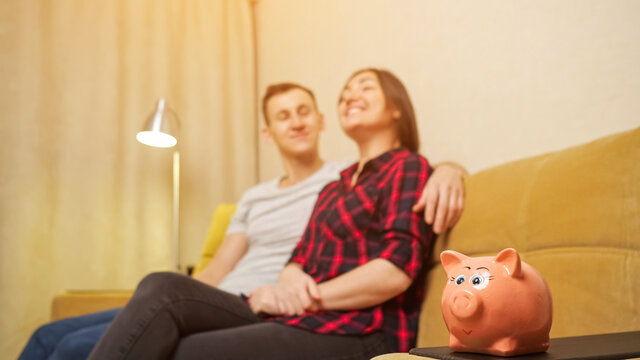Small piggy bank stands on table against blurred young husband and wife sitting on yellow sofa and planning new house building close view