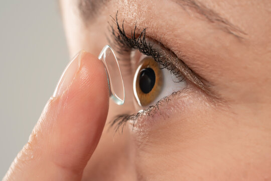 Close-up shot of young woman wearing contact lens