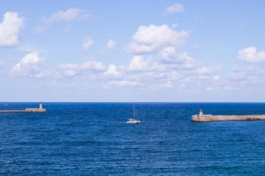 Landschaft mit Segelboot und Leuchttürmen in Valletta, Malta