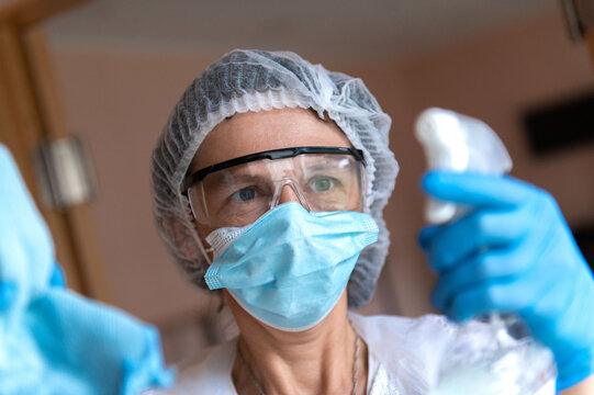 Mature woman in protective medical suit and respirator mask desinfecting furniture and cleaning at hospital.