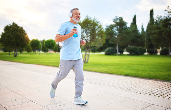 Happy senior man in headphones listening music while jogging outside in city park