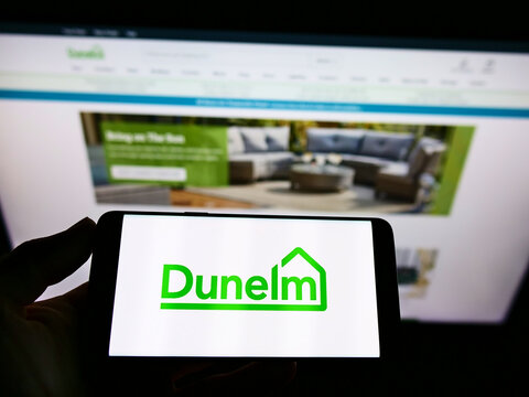 STUTTGART, GERMANY - Mar 06, 2021: Person holding cellphone with logo of furnishing retailer Dunelm Group on screen in front of webpage